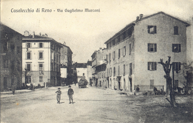 Via Marconi, a destra l'inferriata che funge da parapetto della fontana del Popolo, vicino al palazzo del Tramvia (Archivio fotografico Biblioteca C. Pavese)